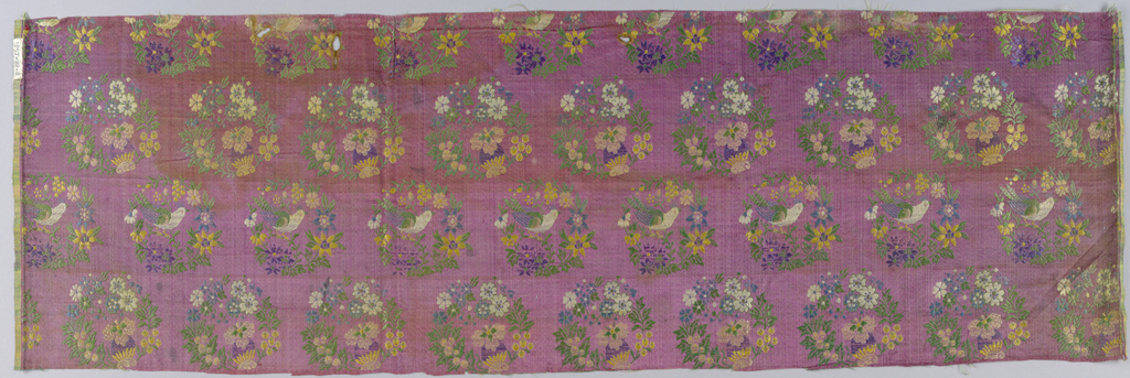 Small circular floral medallions in brightly-colored weft floats are closely set in staggered rows on faded cerise satin ground. Alternate rows have a crested bird.