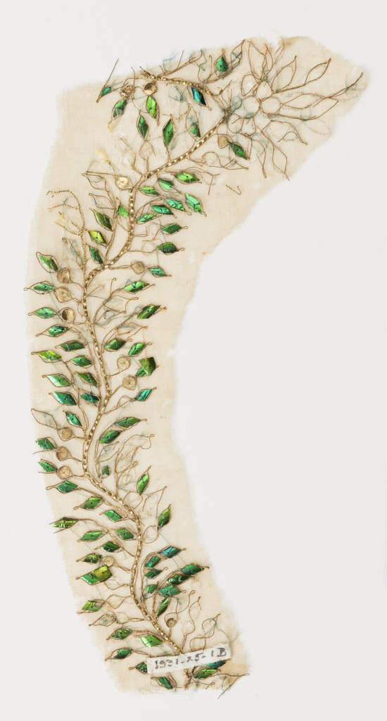 Very sheer ivory cotton muslin embroidered with clusters of flowers and a vine forming a scallop along the lower edge. The vines and stems are formed from crimped gold foil strips, the flower petals from gilt sequins, and the leaves from iridescent blue-green beetle elytra.  Component (A) has ten pattern repeats, with partial bottom vine border.