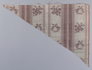 Upholstery fabrics of pale orchid. Ground of moire with vertical satin stripes. Over the moire areas small floral groups and wreaths in satin. Triangular in shape.