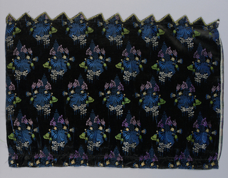 Fragment of a dress silk with an allover design of floral sprays and a lace pattern in blue, green, purple and white. On a black ground.