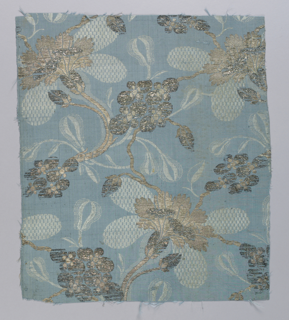 Blue fabric with large scale flowers and buds in a lighter blue; brocaded with two kinds of silver thread.