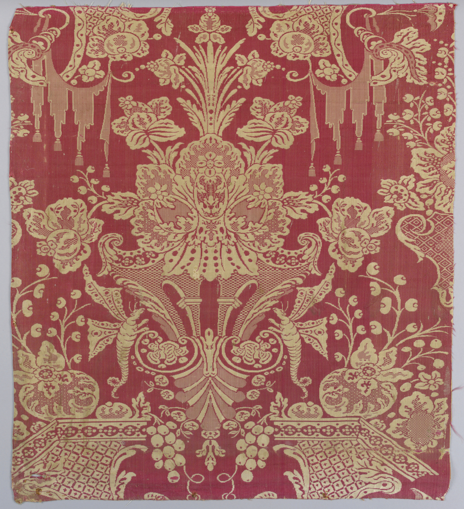 Grotesque style symmetrical design of winged worms, plant forms and architecterual details in red and cream.