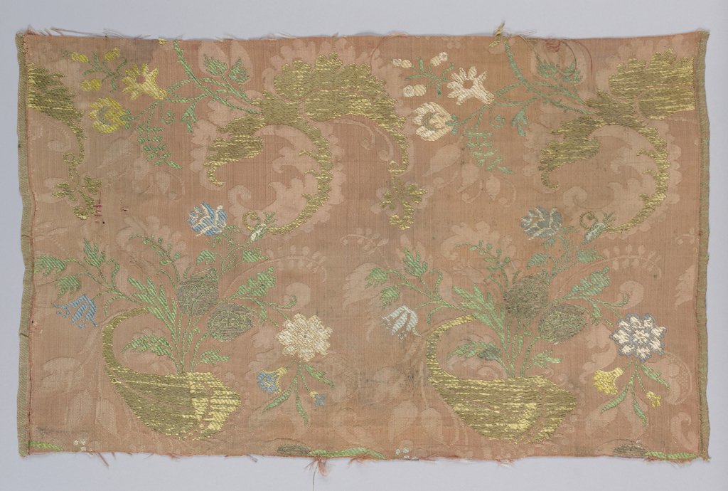 """Fragment of brocaded silk damask  in the """"bizarre"""" style. Red ground with details brocaded in metallic yarns and yellow, green and white silk, showing foliate curves, flowers and gourd-like shapes. Both selvedges present."""
