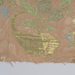 "Fragment of brocaded silk damask  in the ""bizarre"" style. Red ground with details brocaded in metallic yarns and yellow, green and white silk, showing foliate curves, flowers and gourd-like shapes. Both selvedges present."