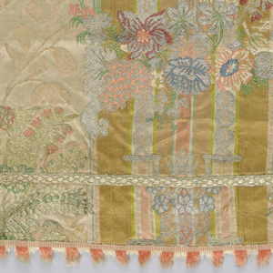 Cornucopia supported by pillars and bracket plus branch of flowers in multi-color silks, silver, and gold on striped damask with related floral pattern. Seams covered by narrow woven tape that also creates a border effect. Salmon and white woven tape with weft fringe at one edge, sewn to four sides.