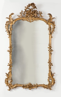 Carved and gilded vertical frame, double arch at top with centered tall pyramid of assymetrical foliage carved à jour and tall curved leaf forms at each corner which flow into serpentine curves and then join straight sides; flowers entwined around straight sides; bottom rail dupicates curve at top rail and has assymetrical group of foliage carved at center.  Mirror made in two pieces.