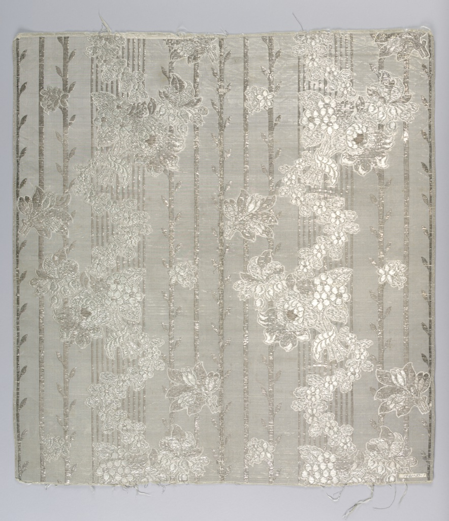 White and silver striped fabric with supplementary weft of flat silver strips whose floats form vertical stripes with leaves at intervals. White floats of the weft form outlines for serpentine floral sprays spread over the striped areas.