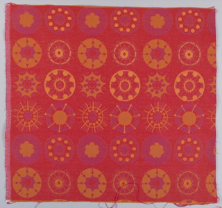 Square of upholstery fabric in red, pink and gold in a pattern showing circular motifs in an allover design.