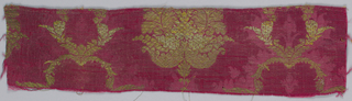 Fragment of dark red silk damask brocaded in gold with a design of a central palmette flanked by slender serpentine leaves and flowers.