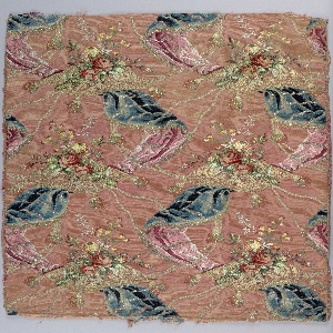 Rose ribbed silk ground, brocaded in colored silks, chenille and gold and silver metal threads. The meander is formed by blue velvet drapery which flips back to reveal pink satin linings; floral sprays rest on brocaded cushions with large tassels at the corners. Red roses are also in pile weave.