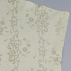 Cream silk with delicate vertical frets intertwined with flowers.