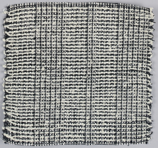 Warp: black and white rovana, Weft: black rovana and ivory asbestos. Plain weave textured with three span floats. Note changes in the alternation of warp colors.