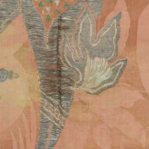 Fragment of brocaded silk damask in the 'bizarre' style. Pink and silver ground with details brocaded in shades of blue showing abstracted florals with long tendrils, and a smoking censer.