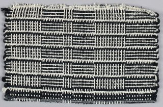 "Warp: black and white rovana, Weft: ivory asbestos and black synthetic (?) Plain weave: changes in alternation of warp and weft colors for rectangles, sometimes called ""log cabin""."