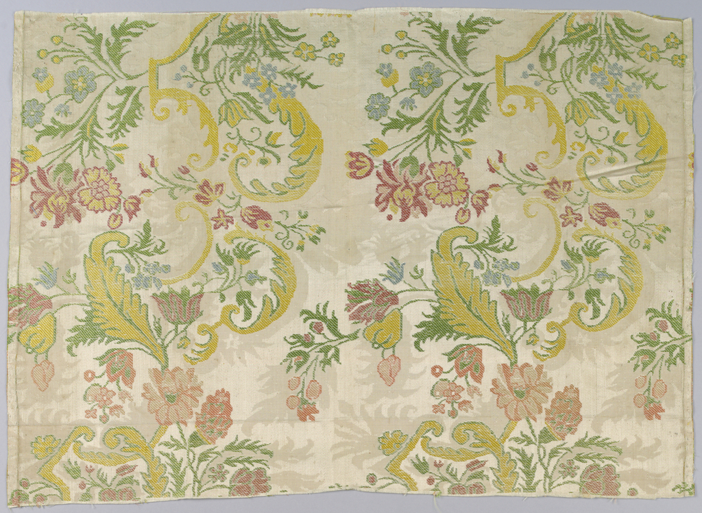 Textile fragment in the 'bizarre' style showing pattern of grey damask brocaded with polychrome florals and strapwork.