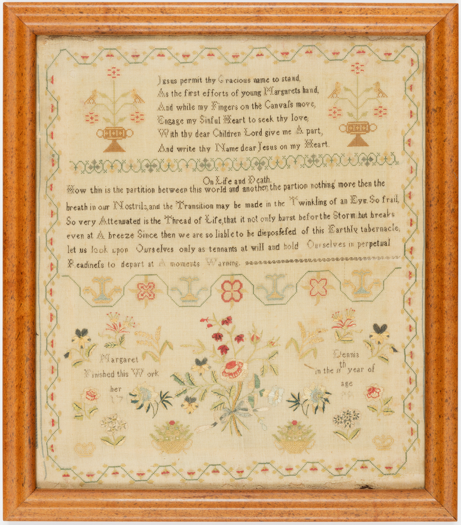 Verses worked in fine black cross-stitch on a natural linen ground, with a bouquet of flowers; stylized running vine borders.