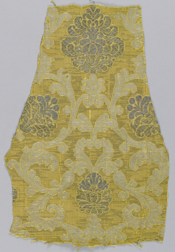Gold-colored silk ground with extra weft of flat silver strips. Symmetrical design of swinging acanthus branches enclosing palmettes which are brocaded in silver thread. White silk extra weft appears in acanthus foliage areas.