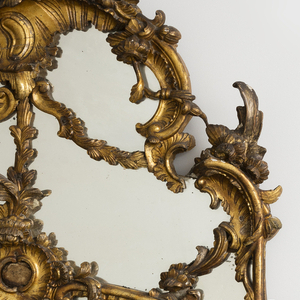 In German 18th century style, with rococo scroll crest entwined with floral branches, with seven smaller plates surrounding a  crested larger plate in the middle.