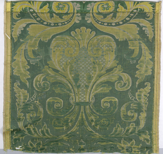 Central palmette with scrolling leaves in green, yellow and white. Both selvages present. Condition worn.