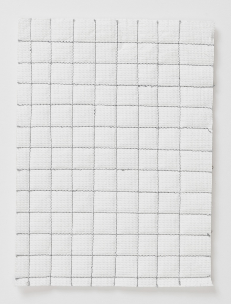 Irregular grid of gray machine stitching on Tyvek. Reverse of Tyvek padded with fiberfill.
