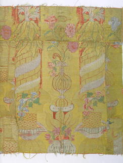 Eight fragments sewn together to form a panel showing 'bizarre' style motifs which include a vase with pink flowers and a spiral column. Rich use of gold and silver with limited brocaded silk colors. Red-orange foundation fabric limited to linear details or small areas of background.