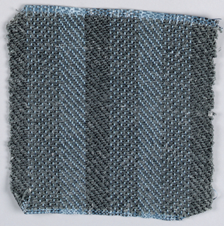 Warp: Blue and black rovana; Weft: grey asbestos, 2/2 twill with changes in warp colors for stripes.