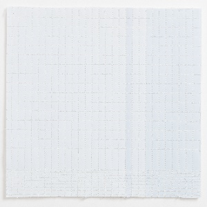 Irregular grid of white machine stitching on paper printed in three shades of pale blue. Backed with fiberfill.
