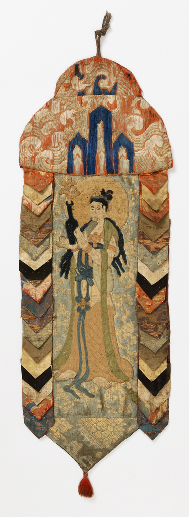 The central figure is a Bodhisattva made by needle looping in the 13th century. The figure was later sewn to a ground of Chinese light blue silk satin with a gold pattern of chrysanthemums on a curving vine. The standard is made from various woven silk and metallic brocades, sewn in tab-like forms to surround the Bodhisattva. A silk tassel finishes the bottom.