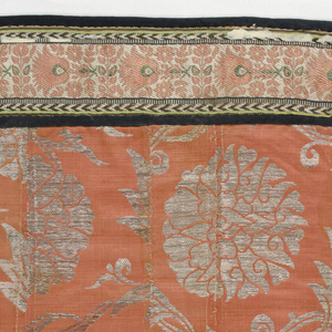 Field of cover made of a patchwork of orange satin fabric brocaded with silver; bordered with woven fabric (Persian?) and piped with black taffeta.