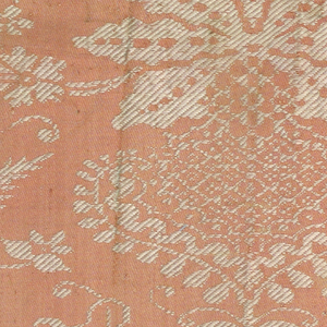 Fragment of silk damask. White and coral showing a symmetrical design of flowering plants with twisting tendrils. Two pieces sewn together; one selvage present.
