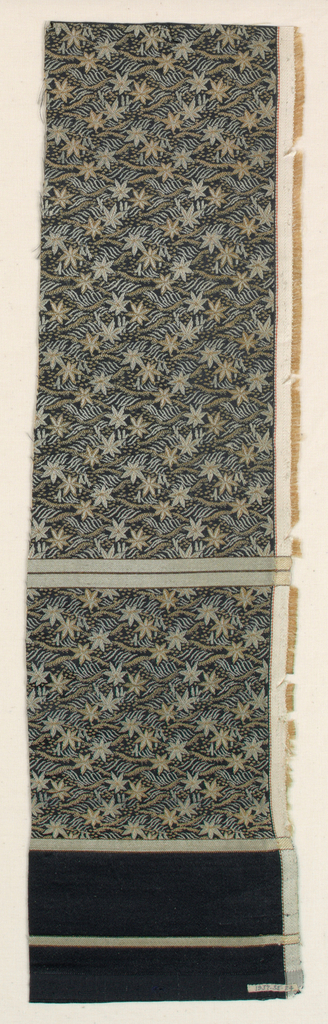 Obi fragment with black silk ground with allover ground figure in tan and white silks. Design of branches forming lozenges and maple leaves. Broad black stripes at bottom.