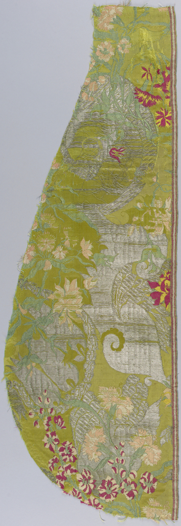 Fragment of green silk damask brocaded with design in the 'bizarre' style showing flowering vines in red, yellow and green with scrolls in silver. One selvage remains.