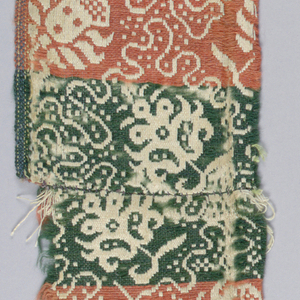 Flowers and scrolling motif in red, green and white.