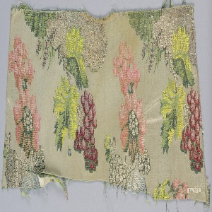 Length of woven silk with a design of branches with large exotic fruits and flowers. In shades of blue, green, yellow, peach, and red, with silver metallics, on an off-white ground.