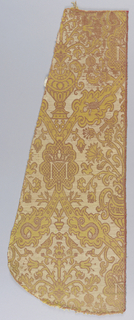 Fragment from a chasuble. Strapwork containing spaces filled with flowering urns alternate with flowering plants. The interstices of the strapwork have an oval space with the letter 'M' on a checkerboard background. Leaf shapes on the strapwork contain snakes and salamanders. Yellow, ivory and reddish purple.