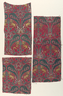 Affronted crowned lions within cartouches in green, yellow and white on red. This is the same design as 1902-1-316 but a different fabric. Among other things the lion's mane is different.