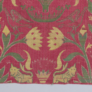 Fragment of woven silk with offset repeating pattern of a carnation symmetrical carnation stem with paired confronted lions and birds. In green, yellow and white on a red ground.