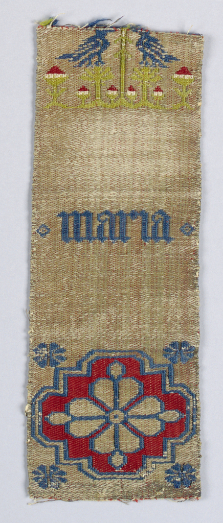 """Fragment of an orphrey with a rosette, paired bird and the word """"Maria"""". Horizontal gold herringbone background with incomplete design of red, blue, and gold rosette at bottom. """"Maria"""" in the center, and green trees with small red and white blossoms with perching blue birds at top."""