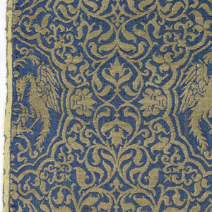 Horizontal rows of medallions edged with small incurving scallops, each containing an ornamental fountain with confronted phoenixes with spread wings and necks bent to drink on either side; small mask at top, bottom, and sides of each medallion. On a close-set ground of floral arabesques in rich gold on a deep electric blue ground. Yellow selvedge on each side; pattern reversible.
