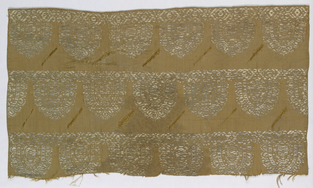 Brown silk with design of oval reticello-like shapes. Both selvages present. Fabric is slashed in a pattern.