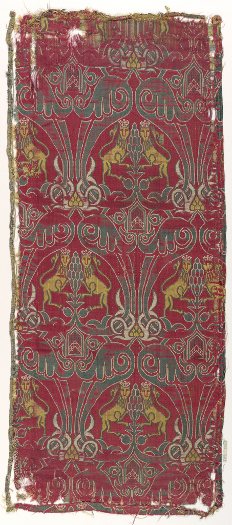 Affronted crowned lions within a staggered arrangement of cartouches in green, yellow and white on red. Selvedge on left.