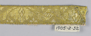 Design of flower and leaves placed alternately up and down. In yellow and metallic thread.