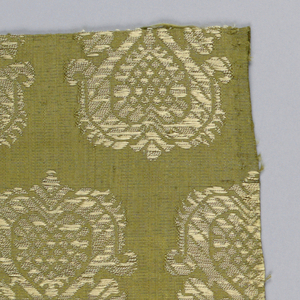 Repeating rows of large metallic palmettes on a yellow-green ground. The orientation of the palmettes alternates each row.