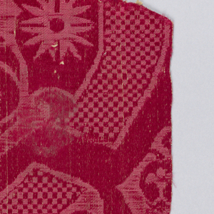 Dark red fragment in a vase design with checked band. Part of a larger pattern.