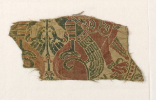 Three fragments of large-scale design of tangent roundels containing symmetrical design of addorsed lions twisting heads around to bite backs of confronted bird-women standing on lions' backs. Twining snakes at back of each bird-woman's neck. Wide borders showing repeats of a man's figure between two griffons (apotheosis of Alexander?), and pearled guard bands. Smaller roundel overlaid at four tangent points of large roundels, with central rosette and inscription border. Interspaces completely filled with large four-pointed rosettes composed of four ornamental tree forms, each with roundel enclosing rabbit-like creature on either side of trunk, growing out of eight-pointed star. Blue-green, dark rose, golden tan, metal brocading now tarnished to dull brown, on cream ground