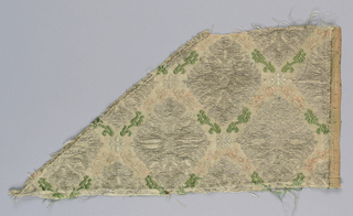Fragments cut from a continuous pattern of gold or silver diamond-shaped floral forms set in a loose diamond lattice made of green, salmon, and ivory blossoms.  The background would have been gold or silver.  Each fragment has one selvage intact.