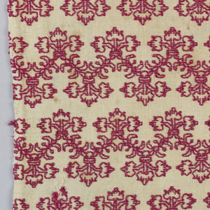 White linen ground with red silk embroidery in horizontal lines of zigzag, symmetrical, three-stemmed, conventionalized floral design.