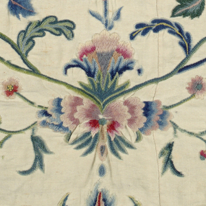 White cotton worked in colored wools; symmetrical design of flower and vine.