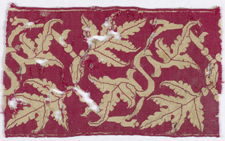 Border fragment showing entwined and pointed leaves in reserve on a red embroidered ground.