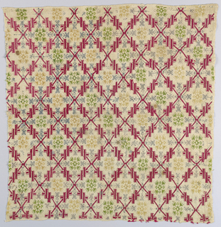 Square cover in a diamond lattice pattern enclosing geometric flowers in red, green, blue and yellow silk on a linen ground.